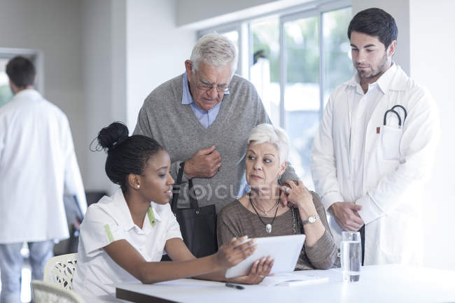 Senior couple at clinic talking to doctor and nurse — Stock Photo