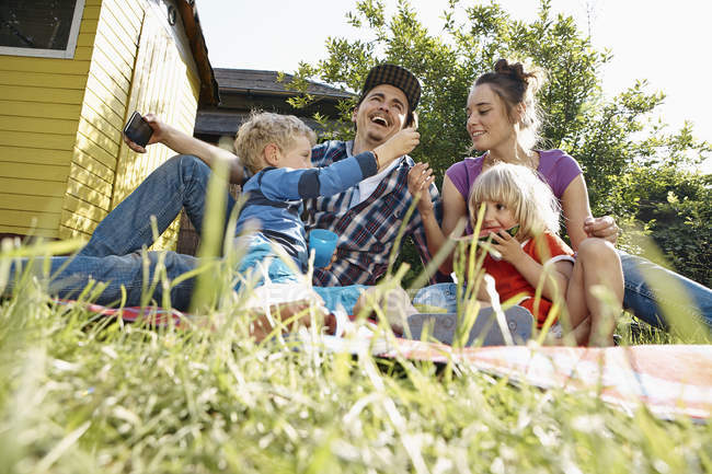 Família feliz relaxando no cobertor no jardim — Fotografia de Stock