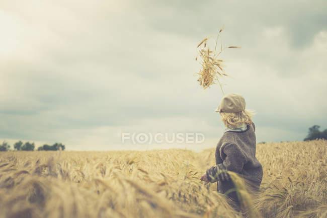 Pequeno menino de pé em um campo jogando picos no ar — Fotografia de Stock