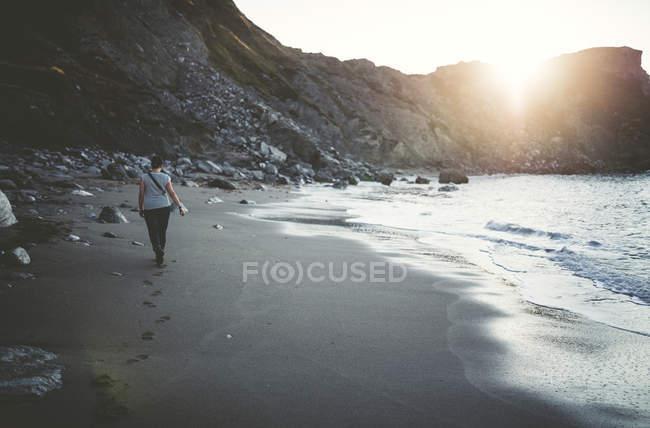 Spain, Ortigueira, woman walking on the sandy beach at twilight — Stock Photo