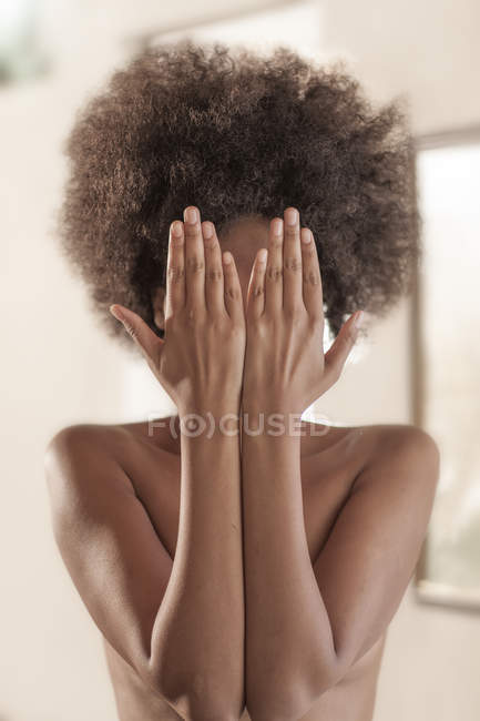 Nude portrait of a young woman hiding face behind her hands — Stock Photo