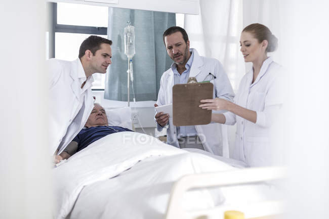 Two doctors, nurse and patient standing in a hospital room — Stock Photo