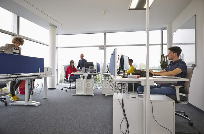 Colleagues working in open-plan office — Stock Photo