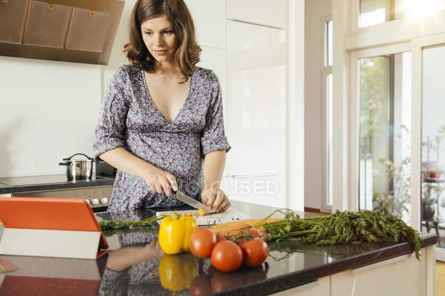 Legumes de corte mulher grávida na cozinha ao olhar digital tablet — Fotografia de Stock