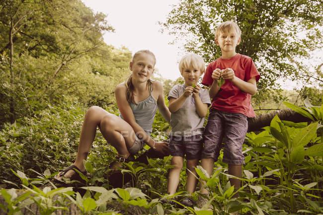 Portrait of three smiling children in nature — Stock Photo