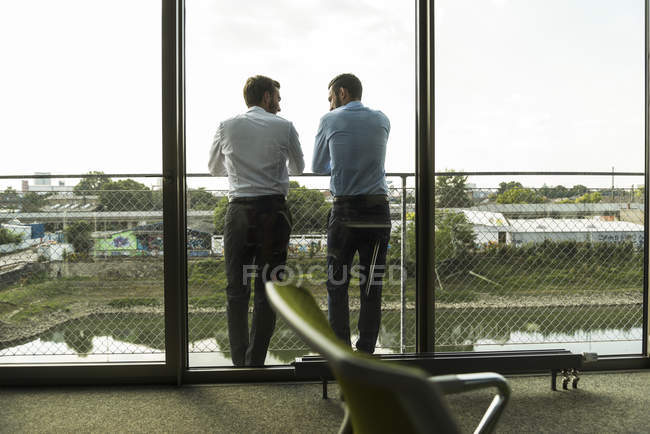 Two young businessmen standing on balcony talking — Stock Photo