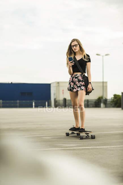 Skateboard de circonscription adolescente à la recherche sur téléphone portable — Photo de stock