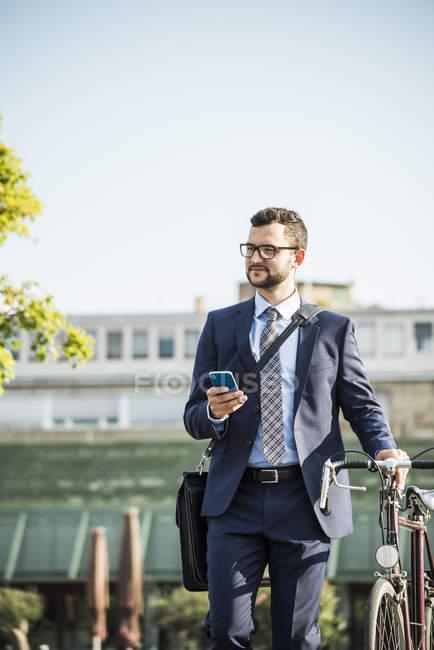 Giovane uomo d'affari spingendo bicicletta, tenendo lo smart phone — Foto stock