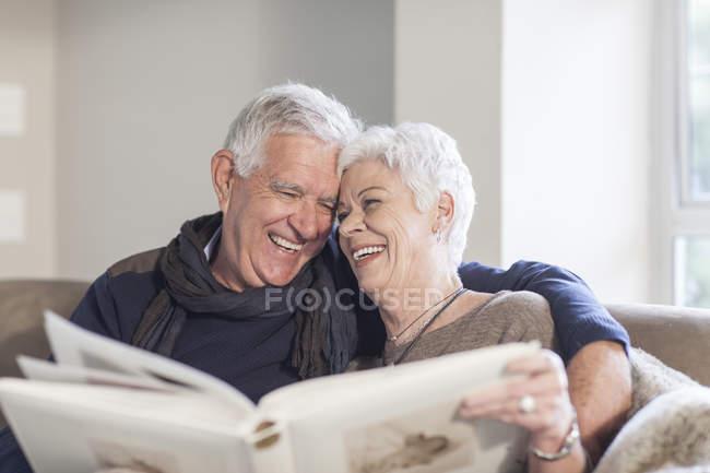 Coppia anziana seduta su un divano con album fotografico — Foto stock