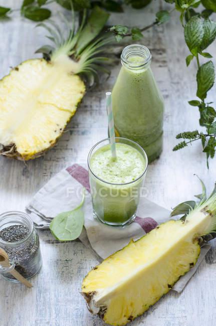 Стекло и бутылка ананасового смузи со шпинатом с чиа и мятой — стоковое фото