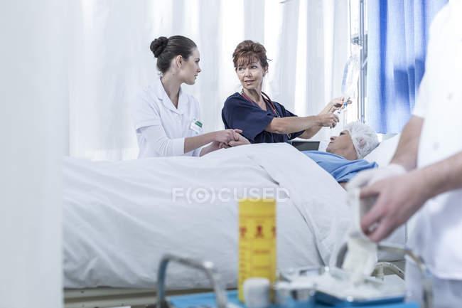 Ärzte in Krankenhausnähe mit liegendem Patienten — Stockfoto