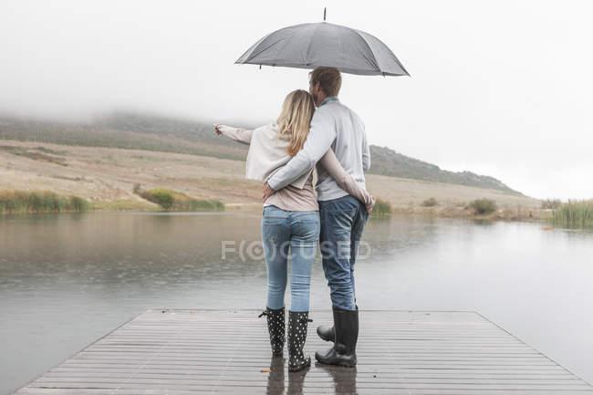 Vue arrière du couple debout bras dans le bras sous la pluie sur une promenade en bois avec parapluie — Photo de stock