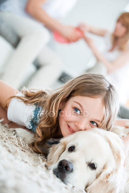 Bambina che stringe a sé con il suo cane, sdraiato sul pavimento, i genitori in fondo a casa — Foto stock