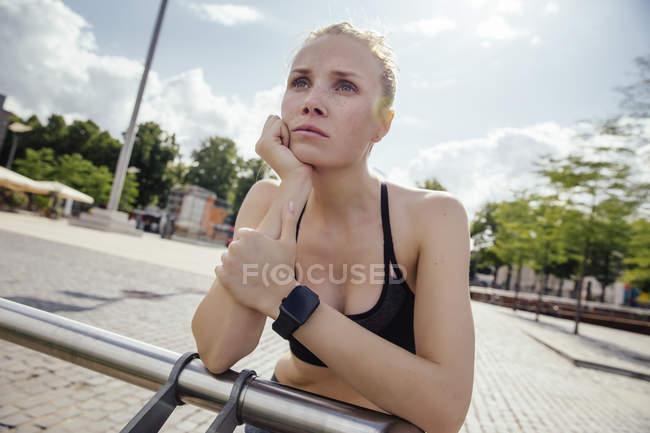 Молодая женщина спортивный с смарт-часы, опираясь на перила — стоковое фото