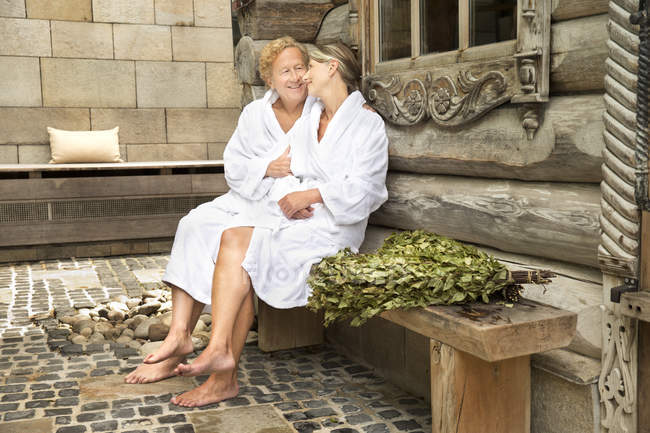 Smiling senior couple in bathrobes sitting outside Finnish sauna log cabin — Stock Photo