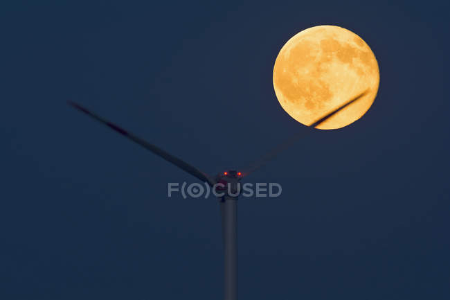 Germany, rise of full moon with wind wheel in the foreground — Stock Photo