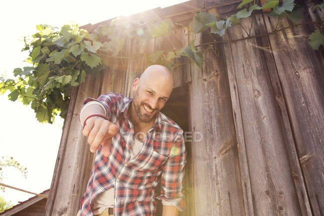 Smiling man standing in front of wooden hut poiting at viewer — Stock Photo