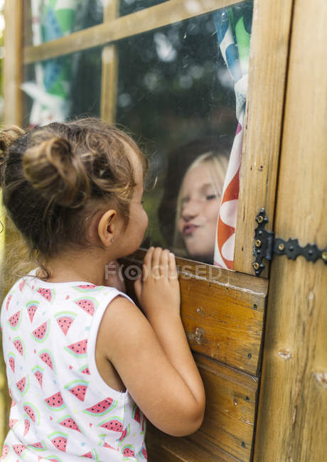 Little girls playing through a glass window — Stock Photo