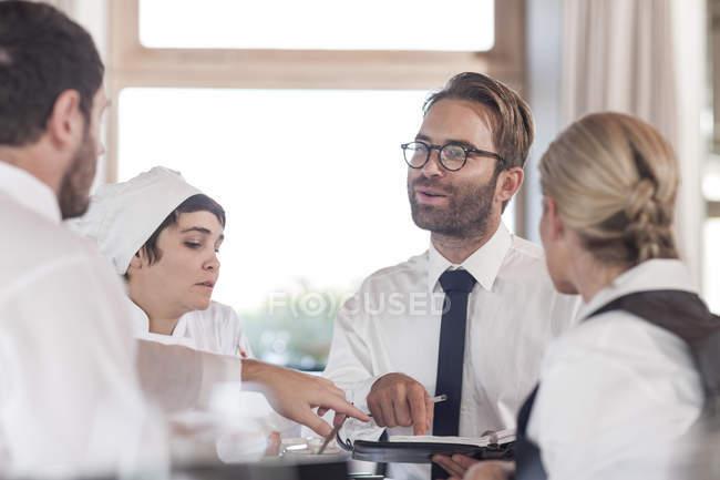 Ресторанная команда обсуждает меню и бронирование — стоковое фото