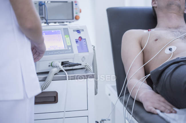 Young man in hospital getting heart rate monitored — Stock Photo