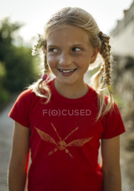 Portrait of smiling little girl with braids — Stock Photo