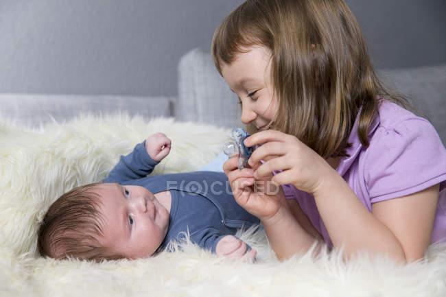 Маленькая девочка и новорожденного брата, лежа лицом к лицу на овчины — стоковое фото