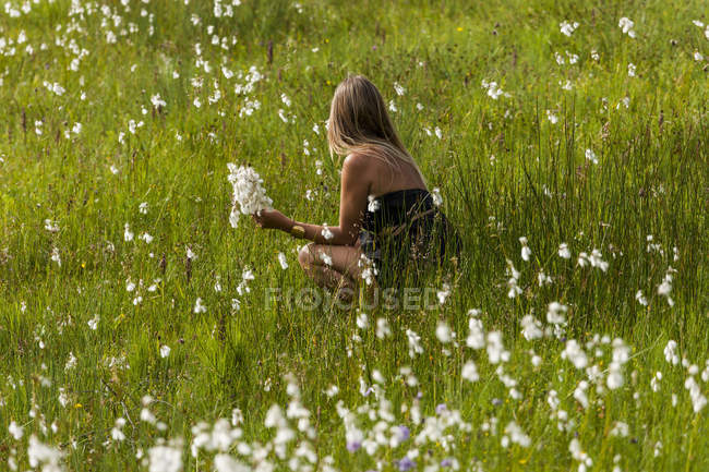 Woman crouching on a meadow picking flowers — Stock Photo