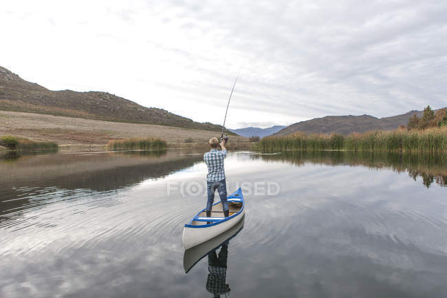 Young man in a canoe fishing on lake — Stock Photo