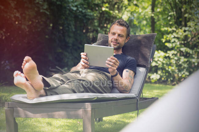 Entspannt im Liegestuhl im Garten unter Verwendung des digitalen Tablet liegenden Mann — Stockfoto