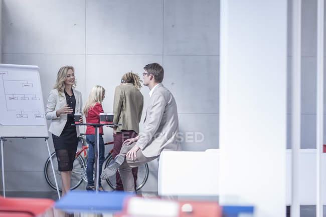 Pessoas de negócios com café para ir comunicando-se em um escritório — Fotografia de Stock