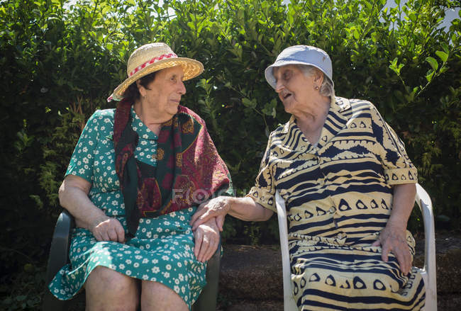 Two senior women communicating in the garden — Stock Photo
