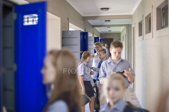 Pupils with teacher talking on hallway in school — Stock Photo