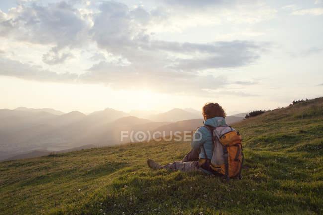 Austria, Tyrol, Unterberghorn, hiker resting in alpine landscape at sunrise — Stock Photo