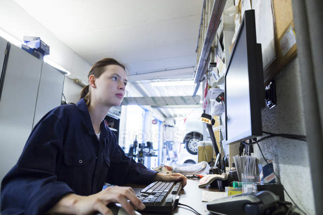 Young woman working in repair garage, writing control report — Stock Photo