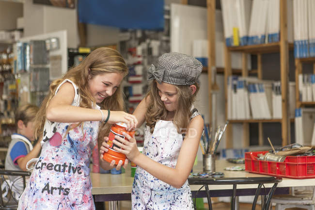 Girls in an art class opening paint bottle — Stock Photo