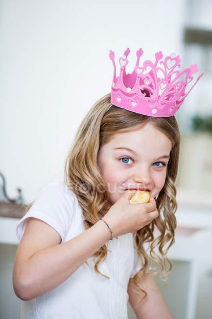 Дівчина носити рожеві корони їдять торт — стокове фото