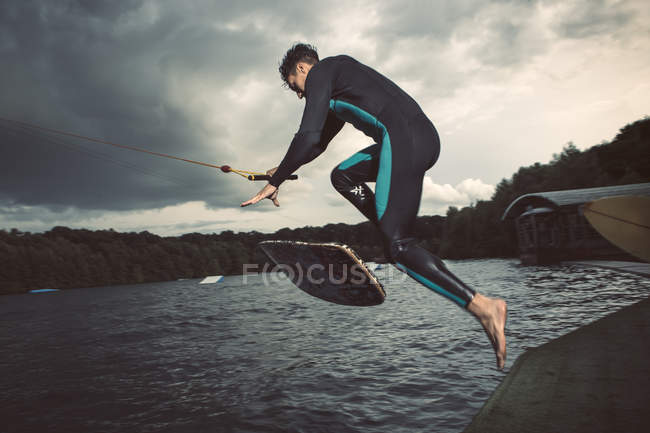 Young wakeboarder jumping in the air — Stock Photo
