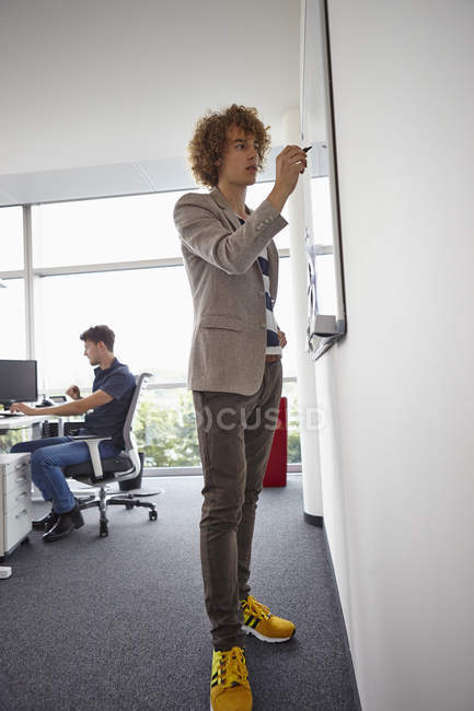 5d9dc20b9 Young man in office writing on whiteboard — color image, two people ...