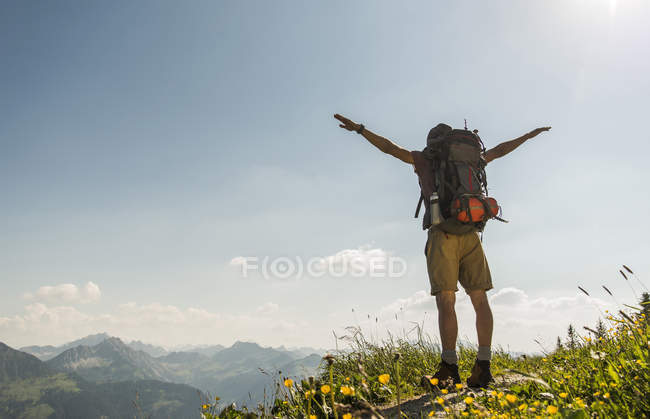 Austria, Tyrol, Tannheimer Tal, young man standing on mountain trail with arms outstretched — Stock Photo