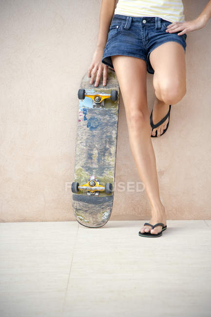 Legs of young woman with longboard in front of a wall — Stock Photo
