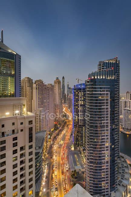 Emiratos Árabes Unidos, Dubai, ve a la calle en el puerto deportivo de Dubái en el crepúsculo vespertino - foto de stock