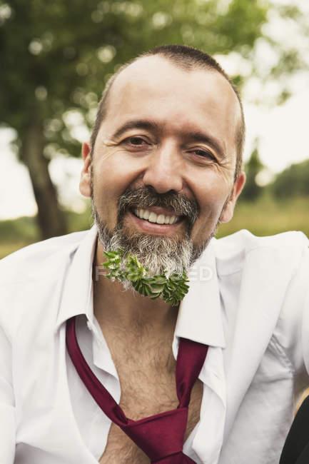 Retrato do empresário sorridente com planta em sua barba — Fotografia de Stock