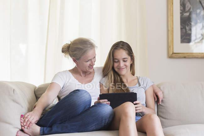 Мать и дочь сидят с цифровым планшетом на диване — стоковое фото