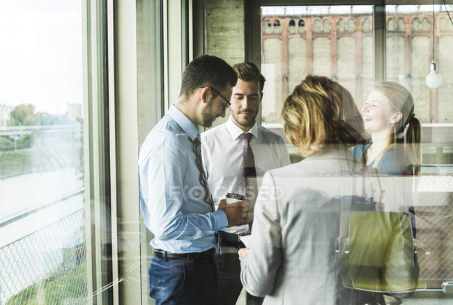 Business people with documents talking at the window in office — Stock Photo