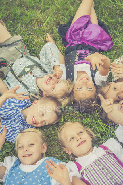 Grupo de crianças vestindo roupas tradicionais deitadas em um prado em círculo — Fotografia de Stock