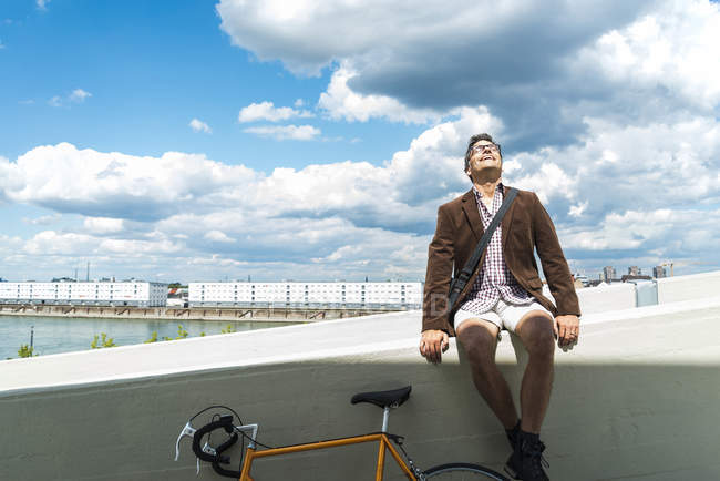 Mature man with bicycle sitting on wall enjoying weather — Stock Photo