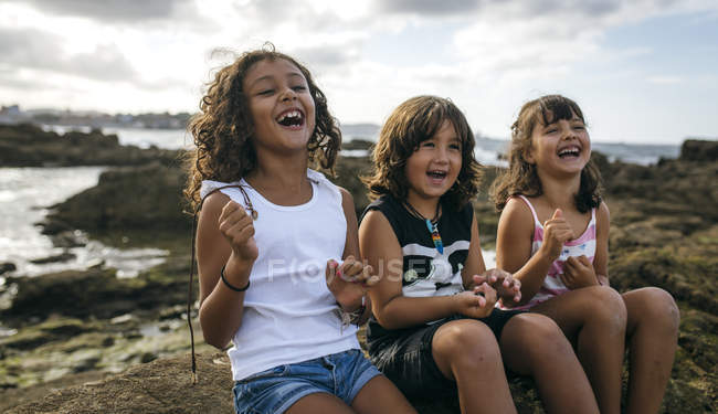Spain, Gijon, group picture of three laughing little children sitting at rocky coast — Stock Photo