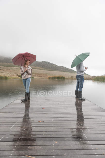 couple standing in the rain on wooden boardwalk with umbrellas