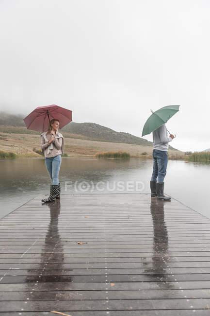 Casal de pé na chuva no calçadão de madeira com guarda-chuvas — Fotografia de Stock