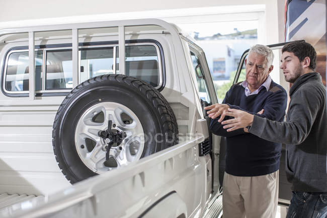 Two men at car dealer examining pick up truck — Stock Photo